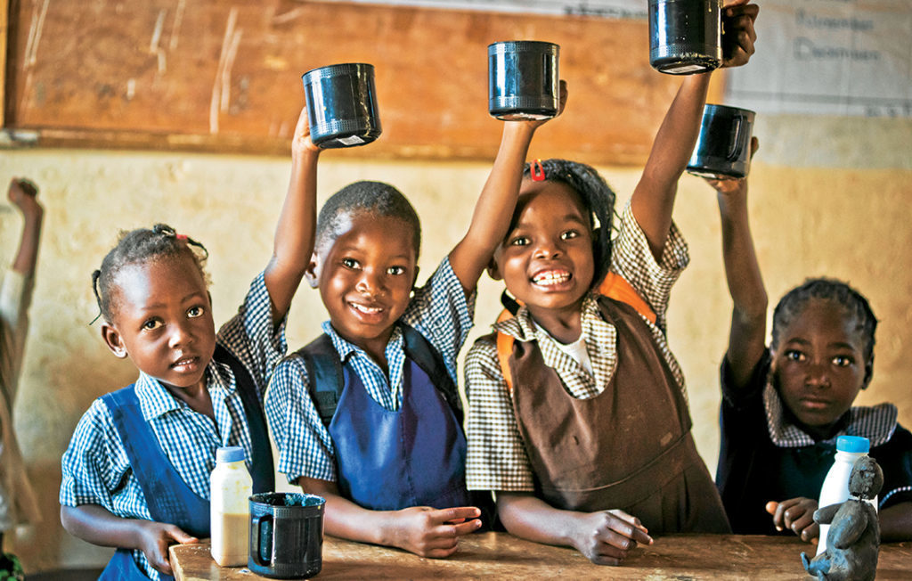 Schoolchildren with mugs of porridge Pic: Chris Watt
