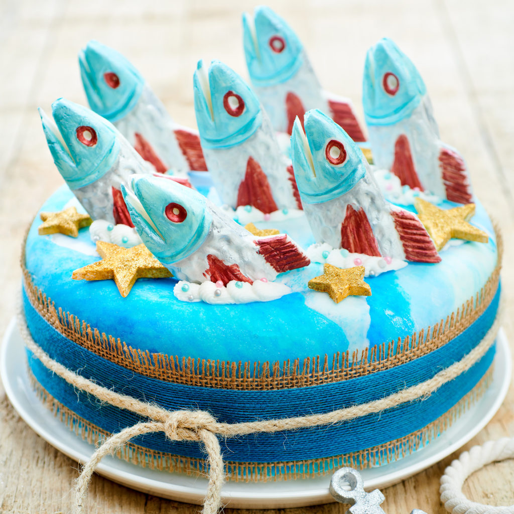 Cake in the style of a Stargazey Pie with chocolate sardine heads sticking up