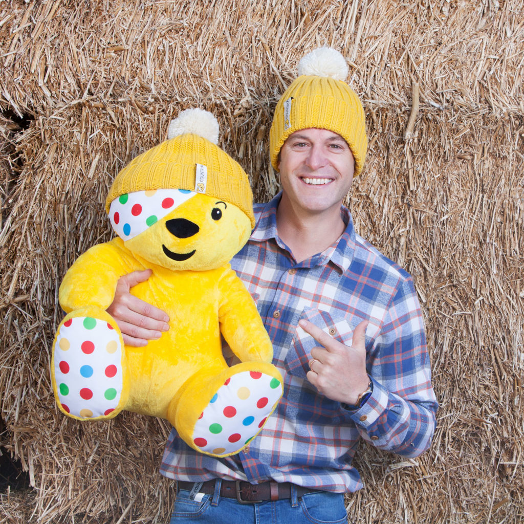 TV presenter Matt Baker with a large Pudsey Bear, both in yellow bobble hats, in front of hay bales