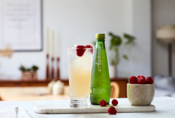 Guava and lychee mocktail in tall glass with bottle of Appletiser