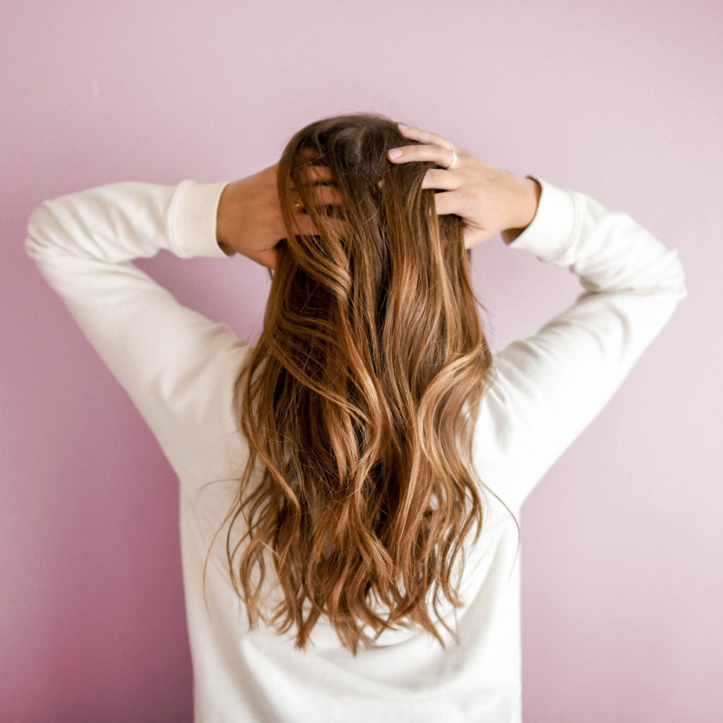 Back view of woman with long tumbling brown hair facing pink painted wall