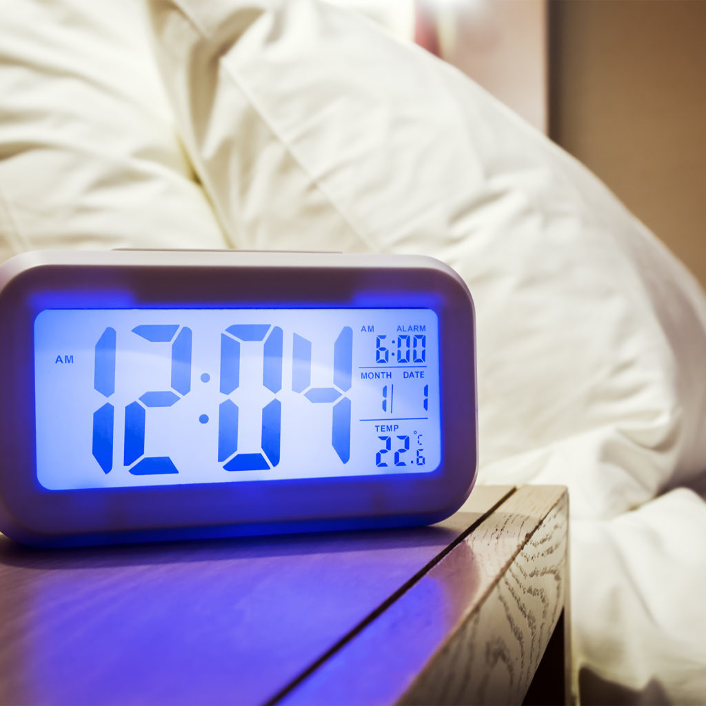 Blue screen electronic alarm clock reading 12.04 on a bedside table, bed and pillows behind