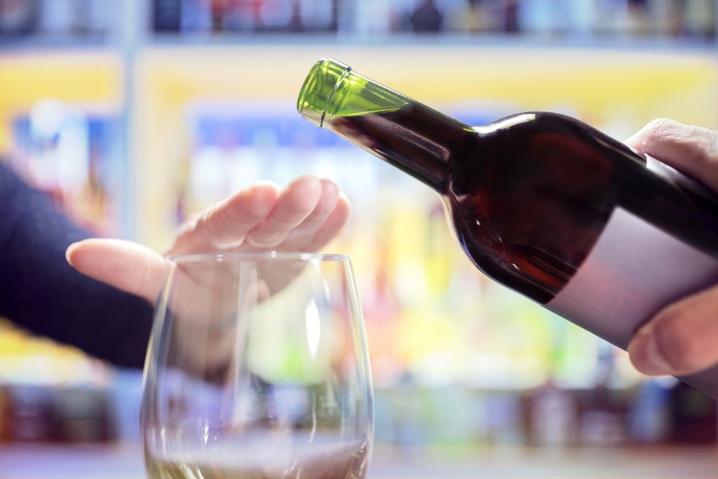 Womans hand covering glass, rejecting more alcohol from wine bottle in bar