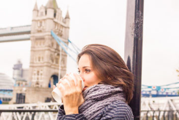 Young woman in a chilly autumn with a soft scarf, warms up drinking from coffee cup.Tower Bridge in the background