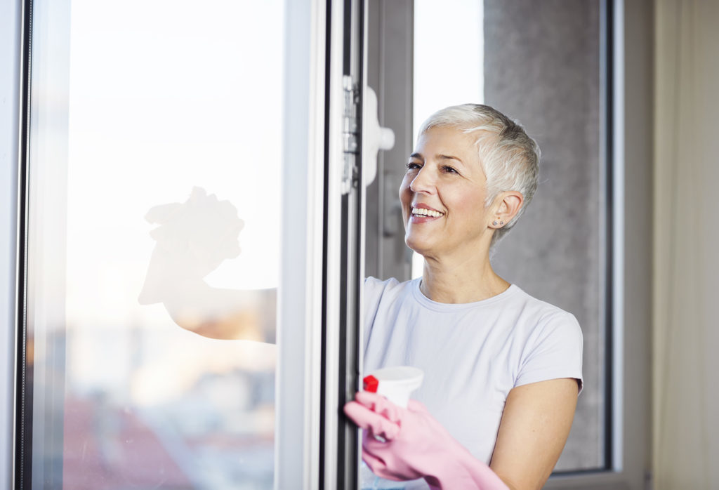 Mature woman cleaning home, washing windows