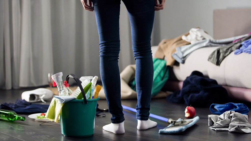 Woman looking at mess in flat and about to clean