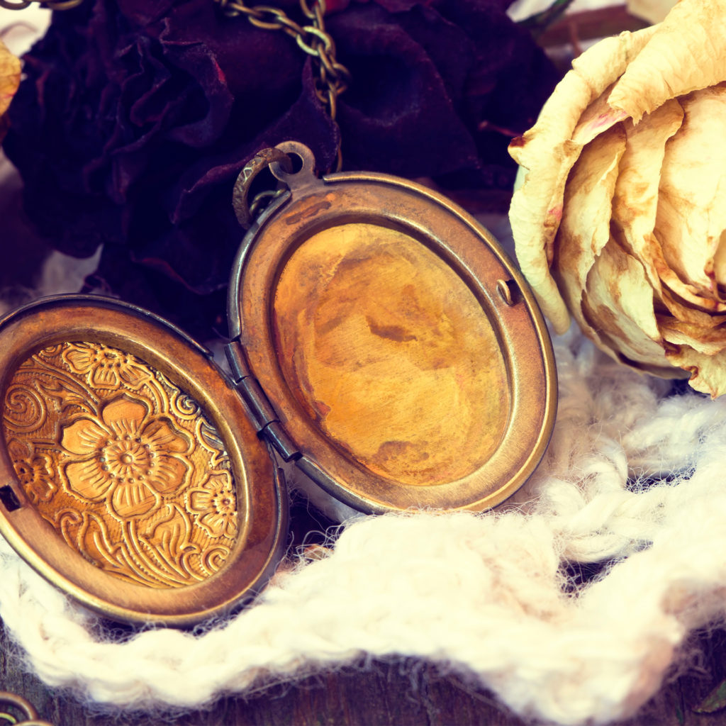 Beautiful atmospheric shot of an old engraved locket lying open with a dried white rose
