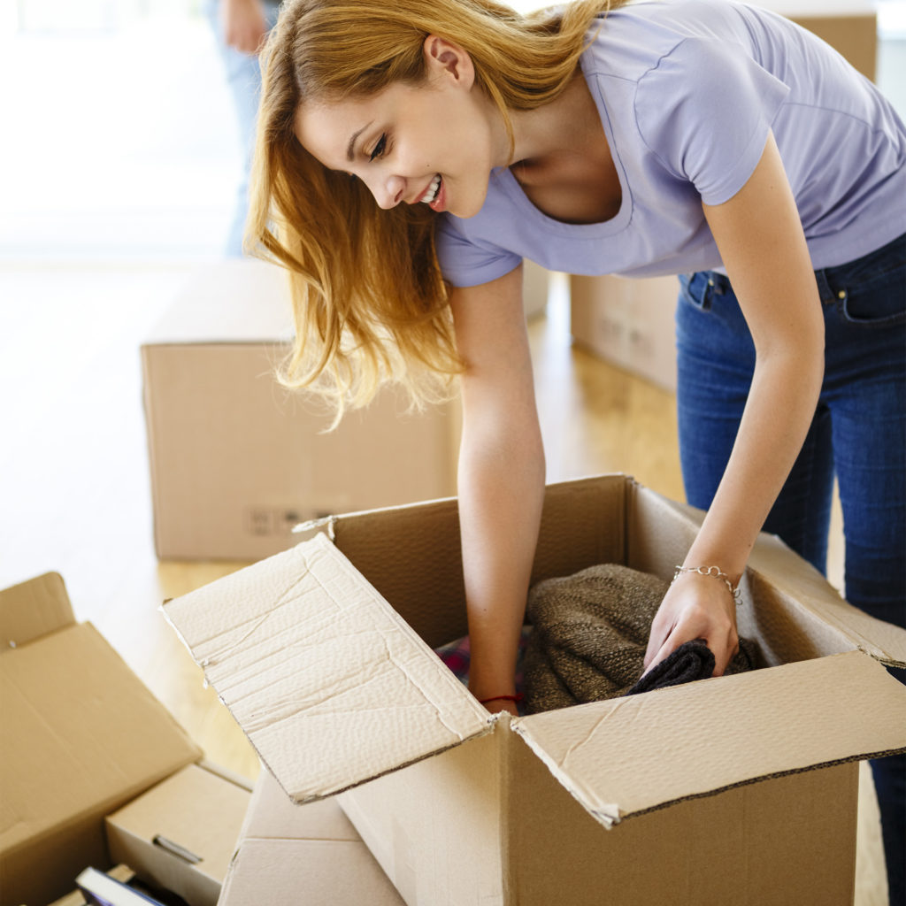 Young woman packing clothes and books into cardboard boxes