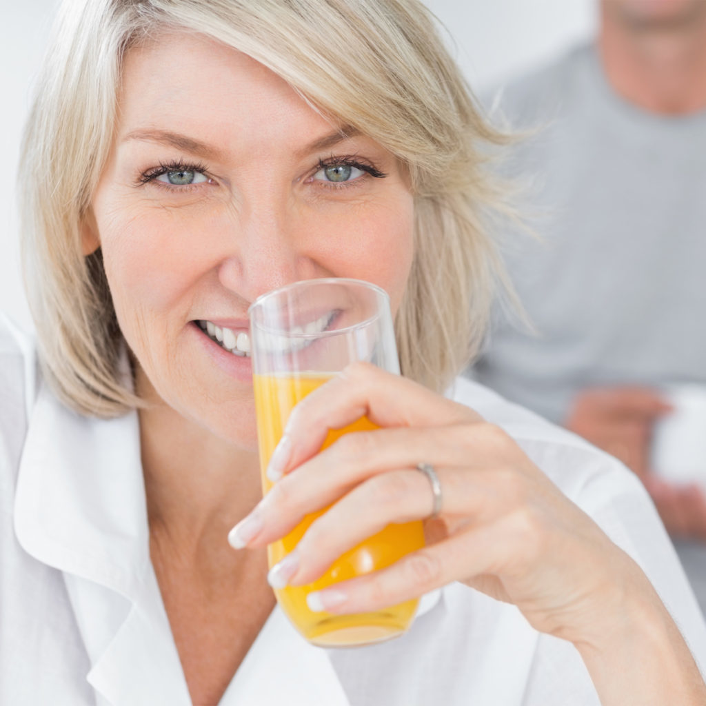 Happy woman drinking orange juice in kitchen with partner standing behind