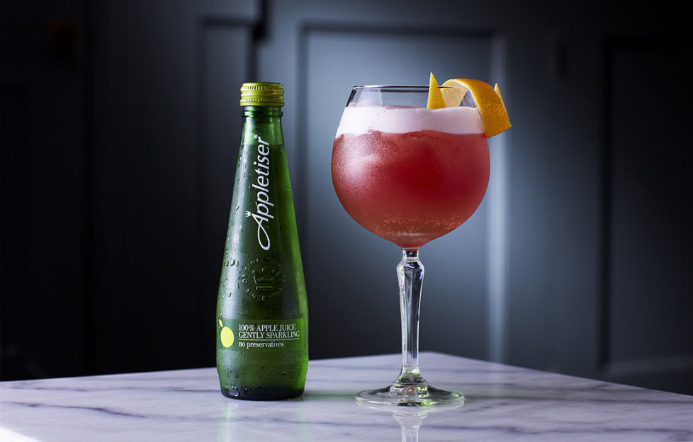 Pink Lady mocktail, deep pink with a head of foam, in large wine glass with a bottle of Appletiser