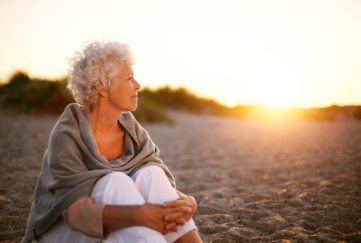 Mature woman with wrap shawl sitting on beach enjoying sunset