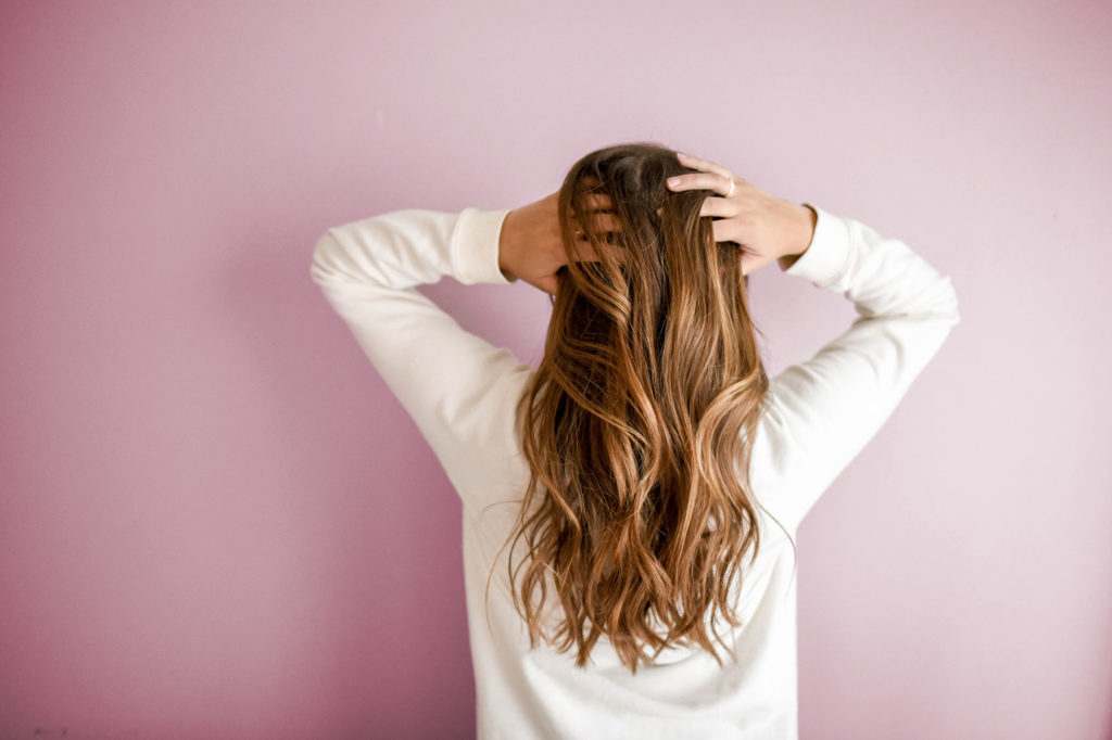 Woman running hands through hair with her back to camera
