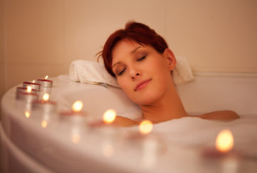 Woman relaxing in a bathtub surrounded by tealights