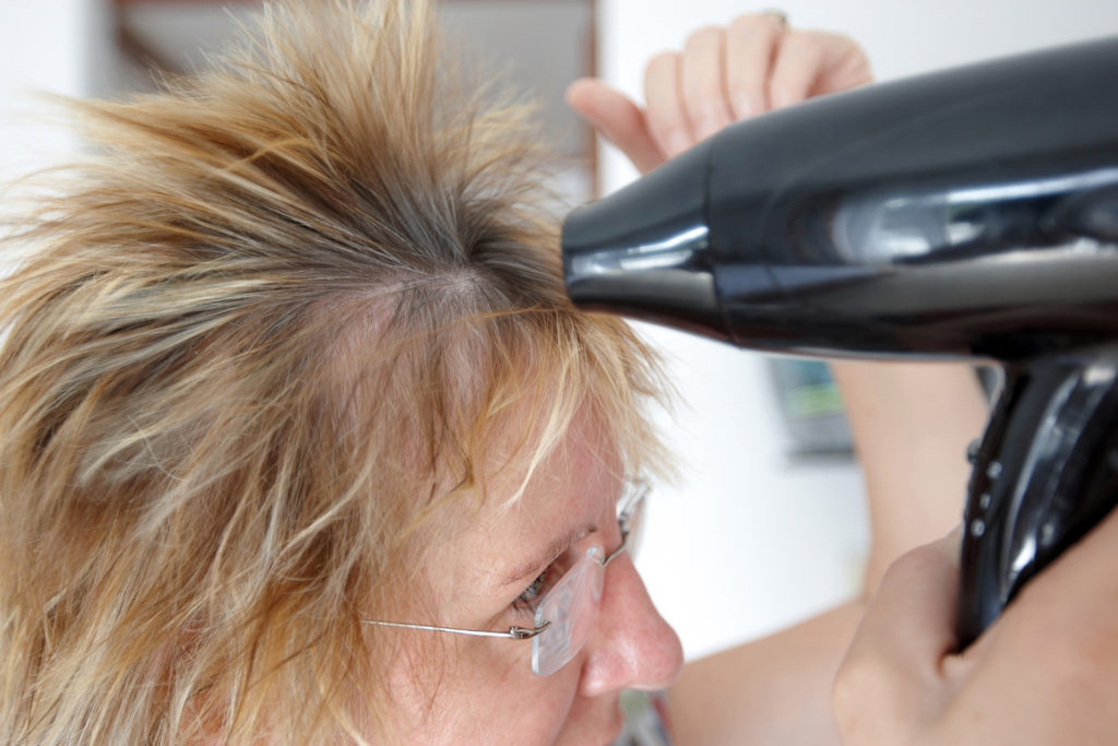 Woman using hairdryer motion blur