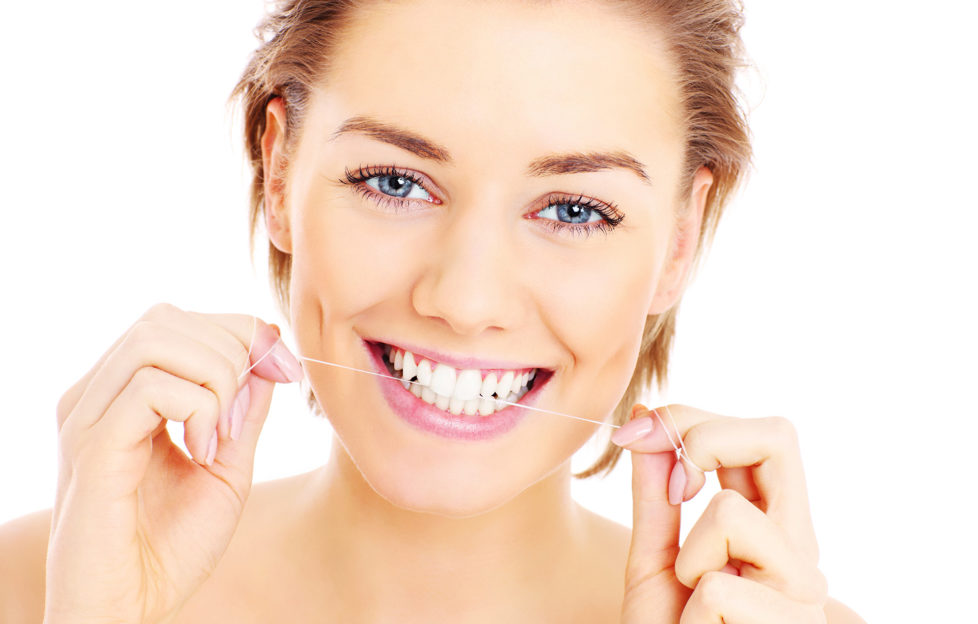A picture of beautiful womanusing a floss for her teeth