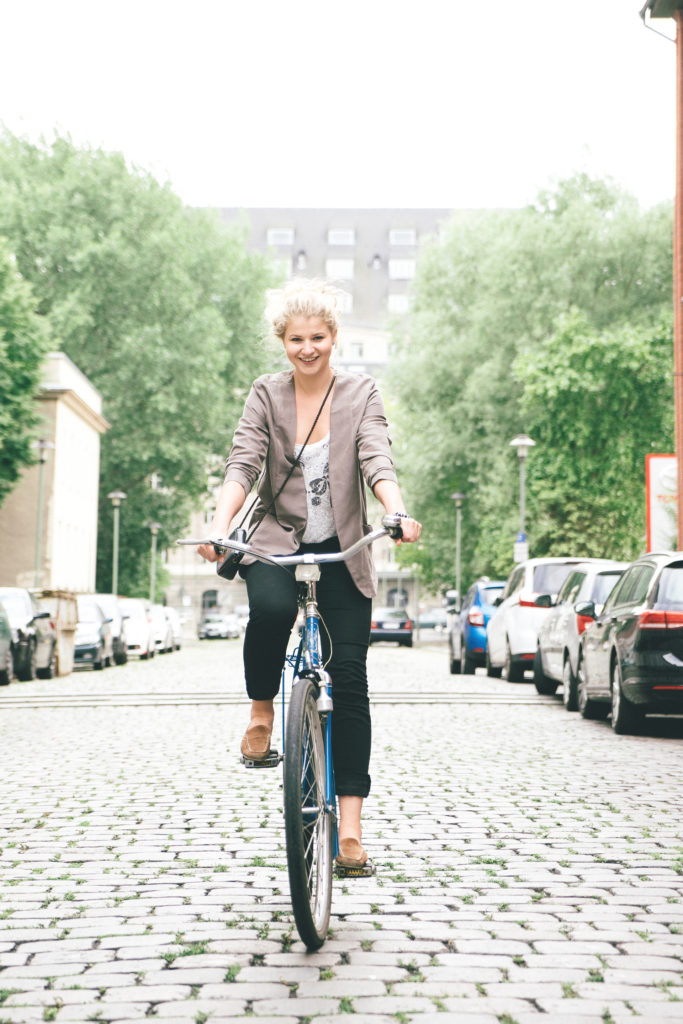 Trendy young woman with her bike, city street on background.