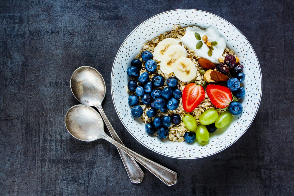 Plate of oat flakes, berries with yogurt and seeds for tasty breakfast on dark vintage background - Healthy food, Diet, Detox, Clean Eating or Vegetarian concept.