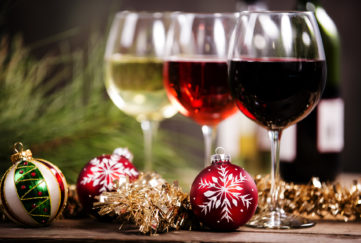 A glass of white, rose and red on a Christmas table with baubles Pic: Istockphoto
