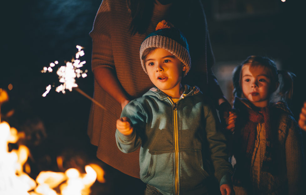 Little boy playing with a sparkler in front of a bonfire on November 5th for Bonfire Night.