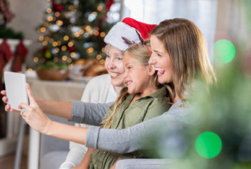 Little girl poses for selfie with mom and grandma