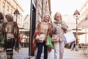 Two senior ladies in shopping. Talking, laughing carrying shopping bags.