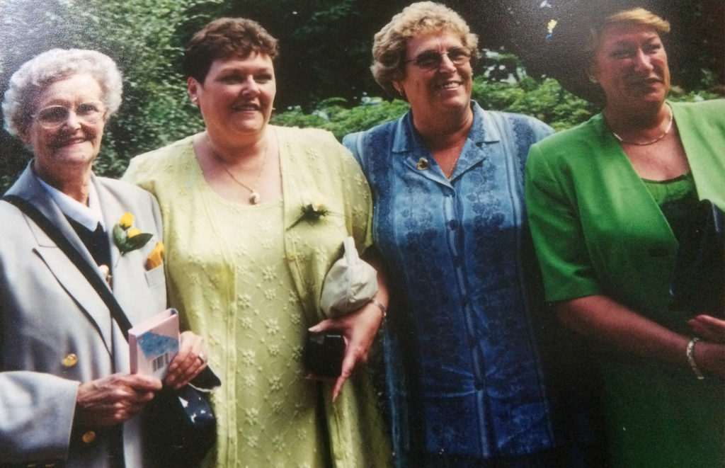 Smiling elderly lady with three mature ladies, her daughters, at a wedding