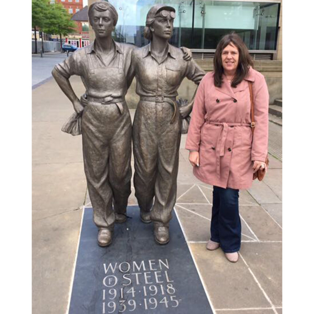 Woman standing beside two bronze statues of female wartime workers