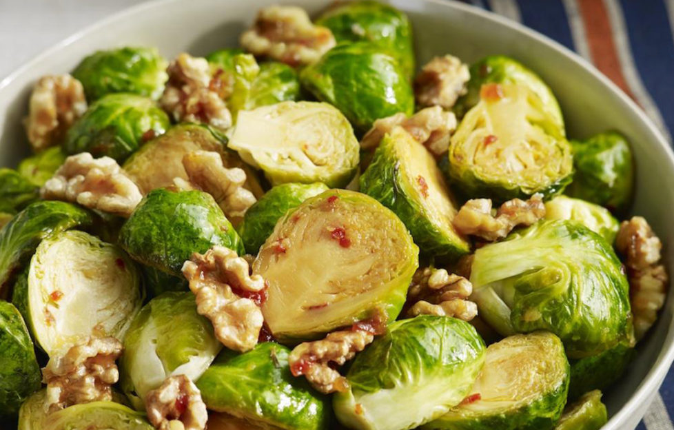 A bowl of Brussels sprouts, sliced in half, dressed with honey, chilli and walnuts