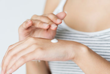Woman rubbing cream into hand.