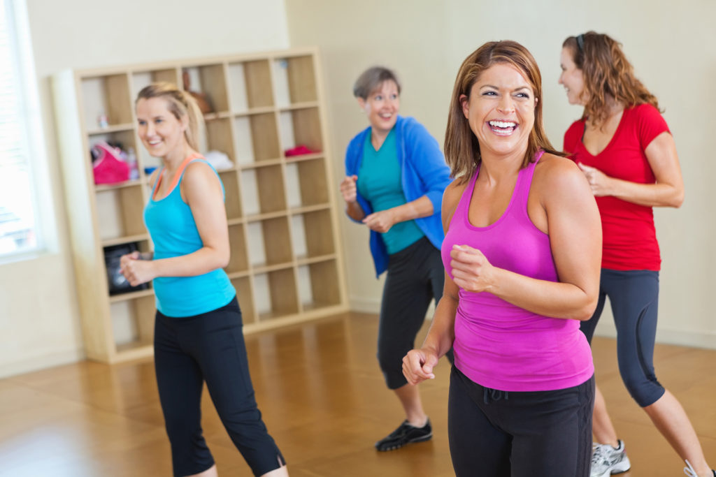 Happy women working out together in fitness exercise class