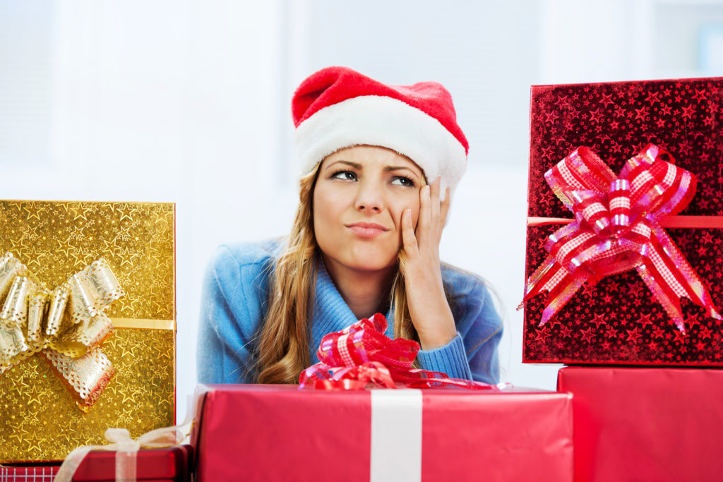 Worried woman surrounded by Christmas presents.