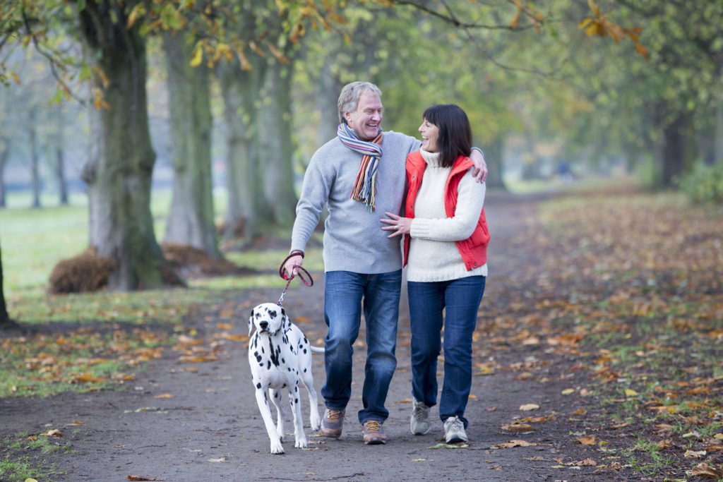 Mature Couple Walking the Dog. Pets make life happier
