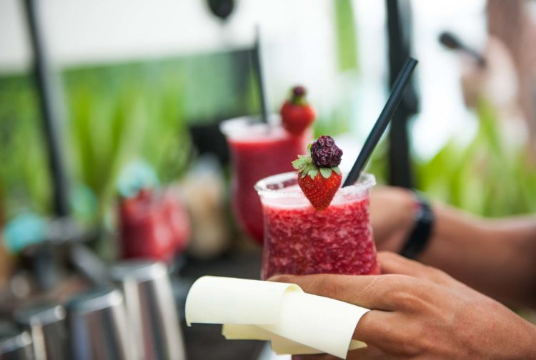 Waiter holding strawberry cocktail, focus on the strawberry