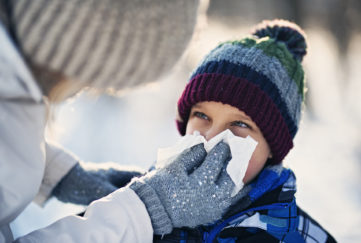 Mother and son having winter walk. Mother is blowing nose of her sick son.