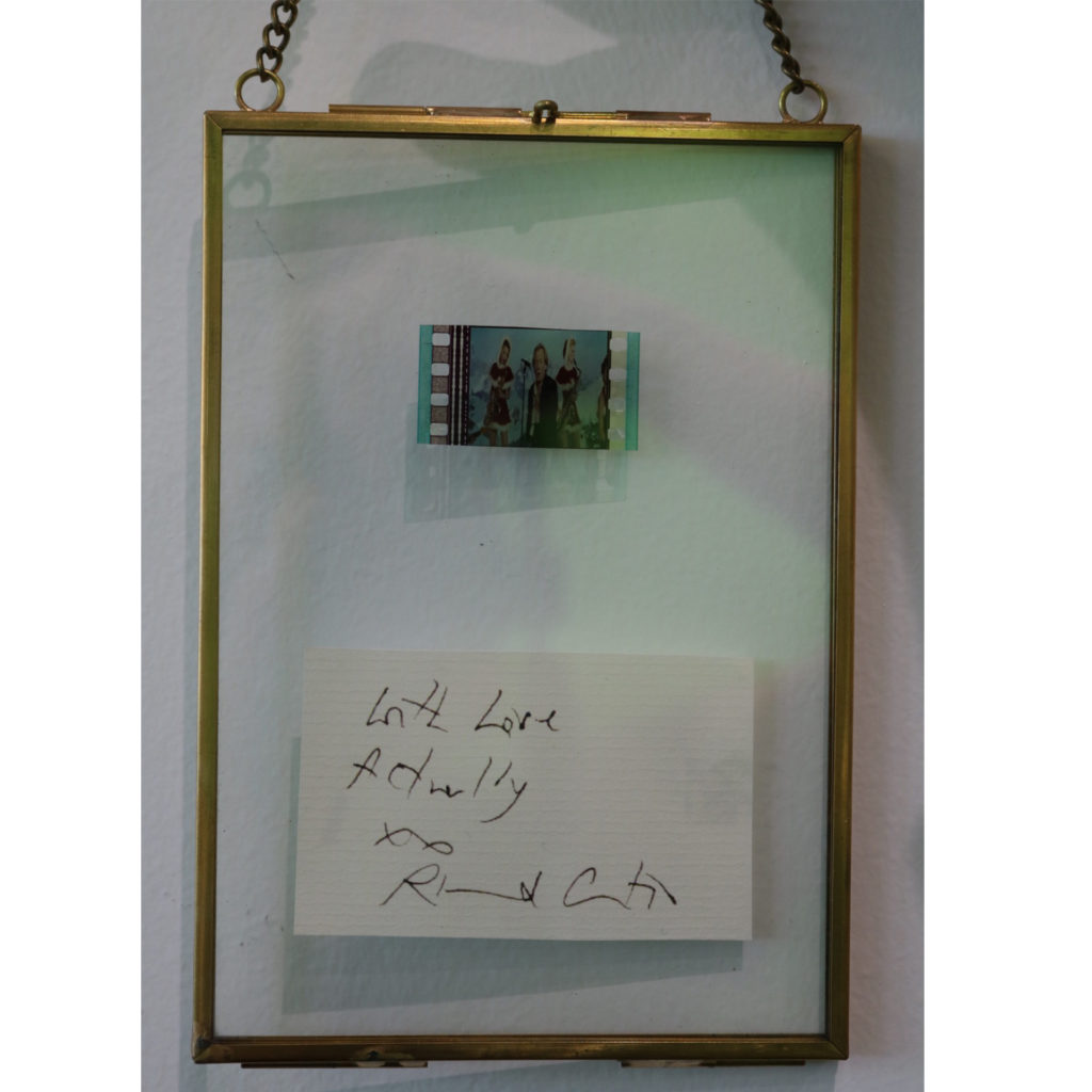 A film cell from Love Actually, in a frame with a signature of director Richard Curtis