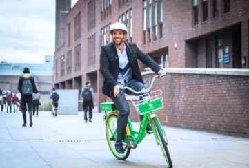 Man with helmet on lime green bike in city centre