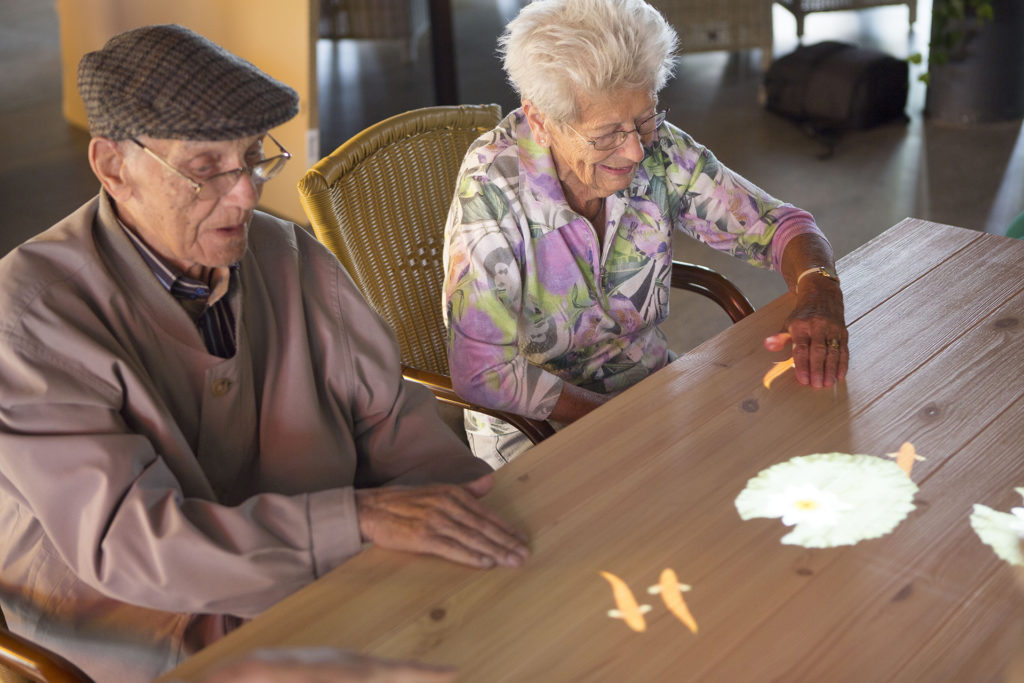 Two older people doing jigsaw puzzle at table