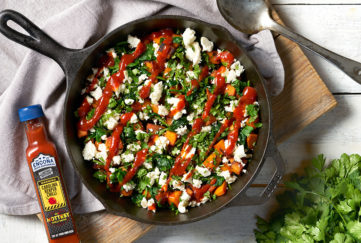 Black iron skillet filled with spinach, sweet potato, feta with a zigzag drizzle of red sauce