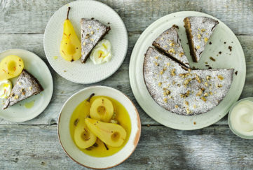 Sugar-dusted cake, 3 slices cut, dish of golden poached pears and 2 small plates with cake slice and a pear