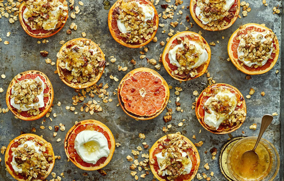 13 grapefruit halves, most topped with golden granola and yogurt
