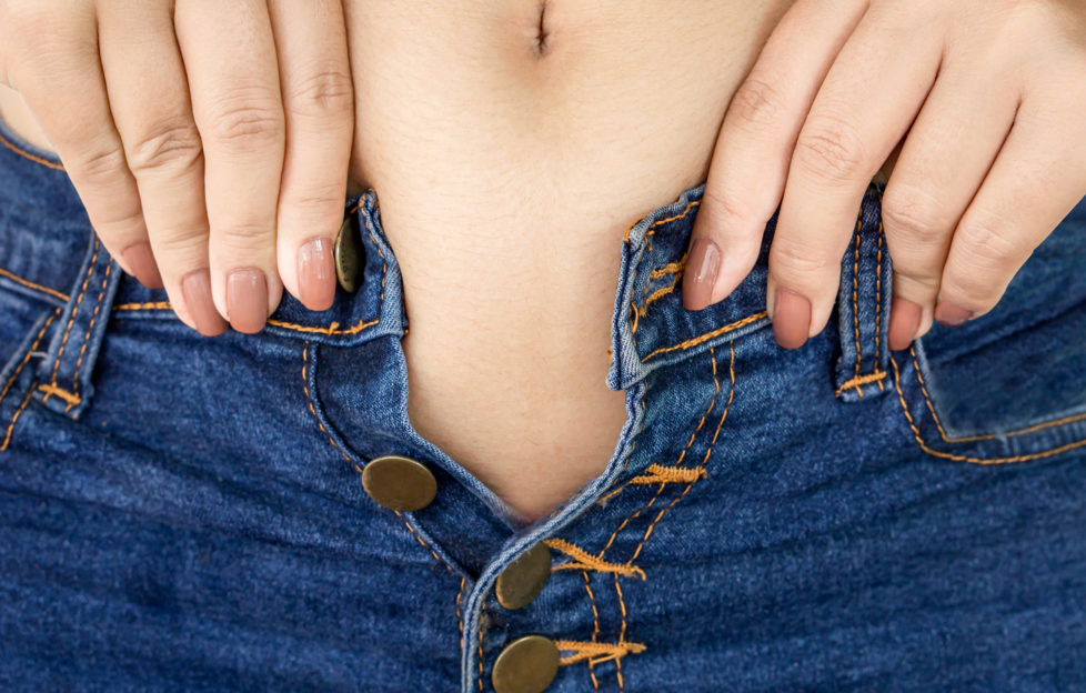 closeup woman hand with big belly try to wear tight jeans