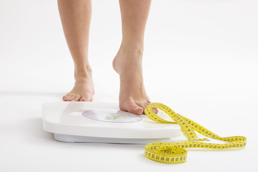 Woman's feet standing on scales with tape measure lying on ground