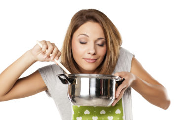 Woman enjoying the smell of food from the pot Pic: Istockphoto