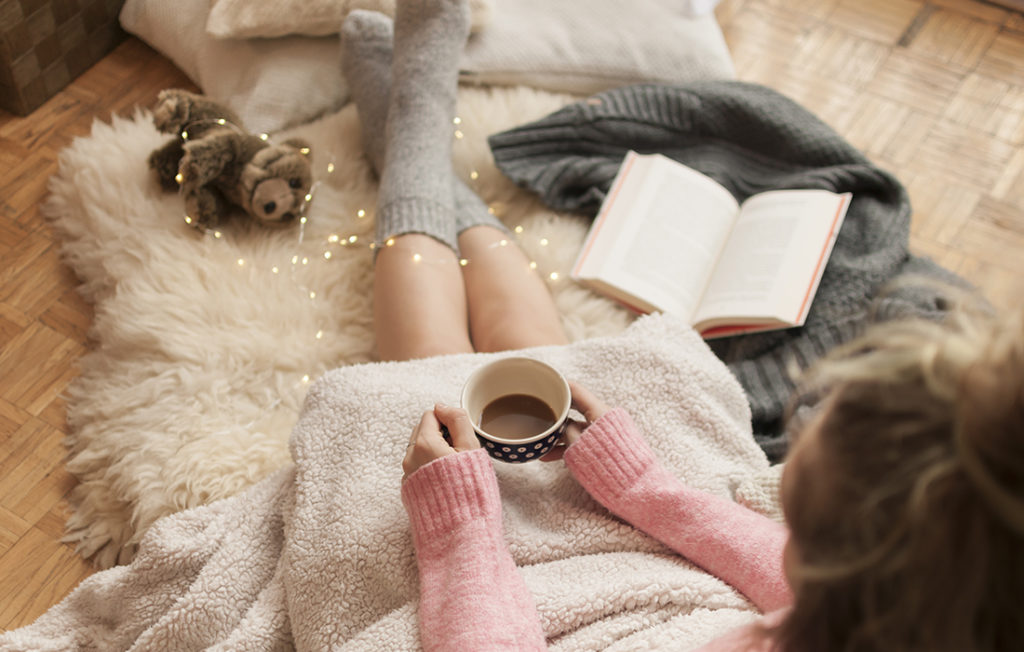 Girl doing hygge with warm blanket, coffee and reading book Pic: Istockphoto