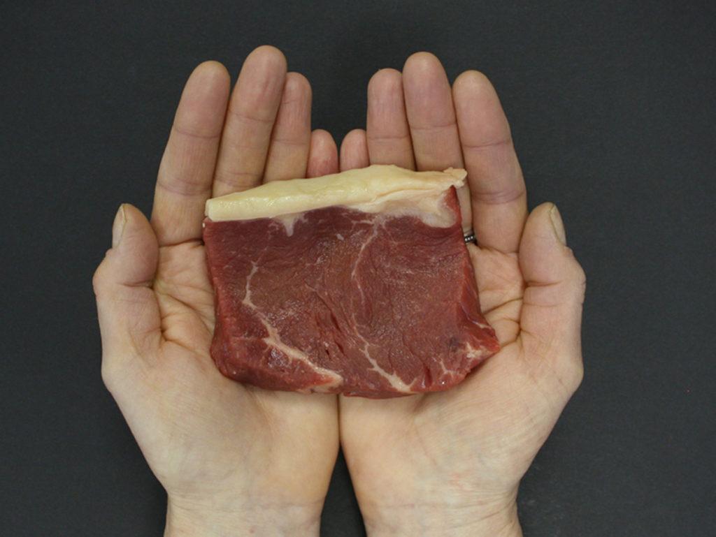 Hands holding red steak