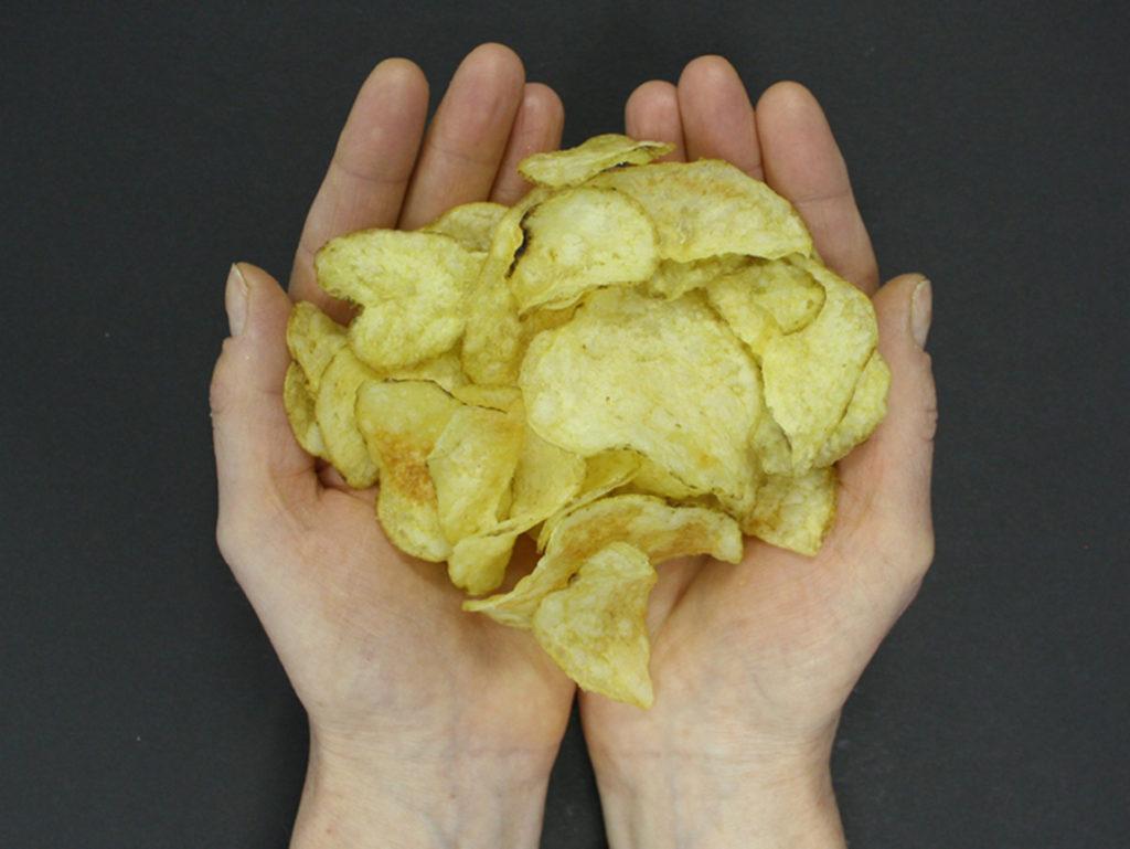 Hands holding crisps