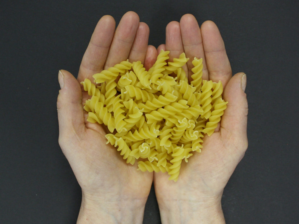 Hands holding pasta