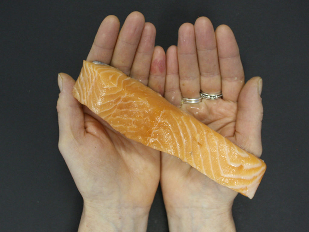 Hands holding salmon