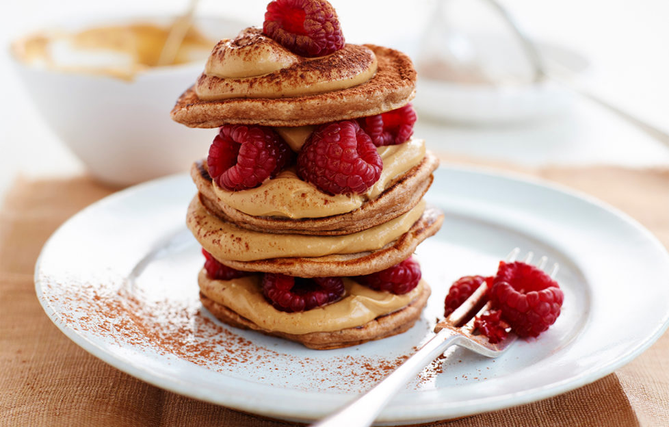Stack of small pancakes layered with coffee coloured mascarpone and fresh raspberries