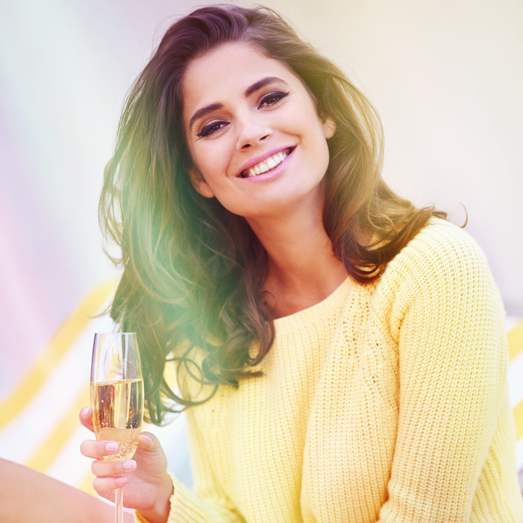 Shot of a gorgeous young woman sitting outdoors holding a glass of champagne